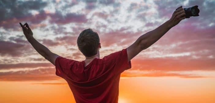 Un homme les bras ouvert devant un coucher de soleil